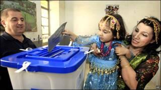 تصویر از یک کودک کرد عراقی که به کمک مادرش در حال انداختن برگه رای به صندوق است