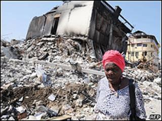 Mujer pasa frente a ruinas de un edificio en Puerto Príncipe