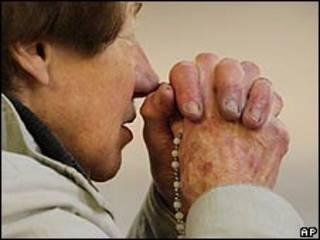 Mujer rezando en una iglesia católica en Irlanda