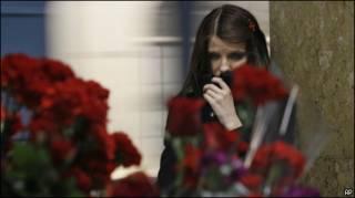 Цветы и скорбязая девушка на месте одного из взрывов в московском метро 29 марта 2010 г.