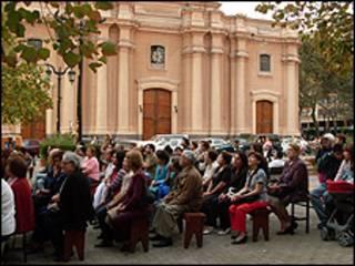 Personas sentadas en la calle oyen la misa