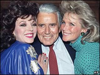 John Forsythe (centro) con las protagonistas de Dinastía Joan Collins (izquierda) y Linda Evans