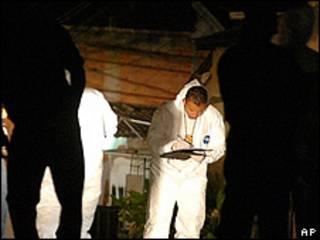 Miembros de la policía inspeccionan el lugar donde fueron asesinadas nueve personas en Tegucigalpa
