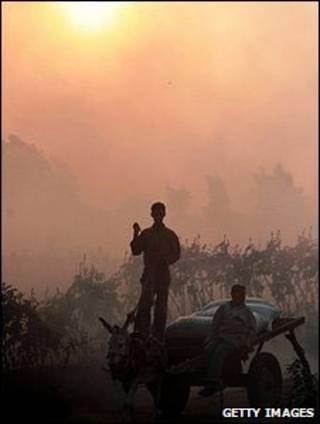 Dois homens em uma carroça envolta em fumaça