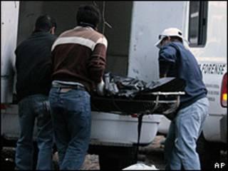 Forenses cargan los cuerpos de seis hombres asesinados en Cuernavaca, campo de batalla de los Beltrán Leyva