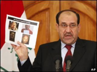 O primeiro-ministro do Iraque, Nouri Al-Maliki, mostra fotos de líder insurgente morto em entrevista coletiva nesta segunda-feira (AP)