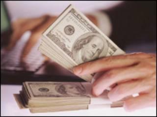 Рука с пачкой стодолларовых банкнот