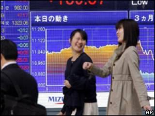 Mujeres pasan delante de pizarra con valores bursátiles en Tokio
