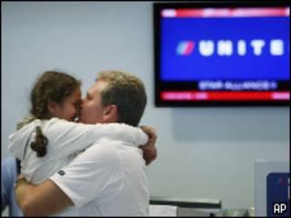 Пассажиры, вернувшиеся домой, на фоне табло авиакомпании United