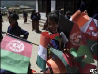 أطفال يلوحون بأعلام الدول المشاركة في قمة بوتان