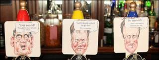 Caricaturas de candidatos en grifos de cerveza en un pub inglés