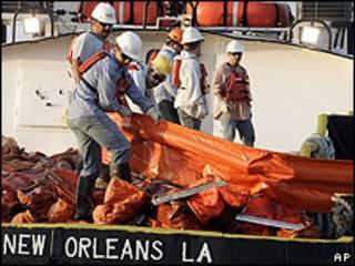 Trabalhadores colocam barreiras para conter vazamento em barco no porto de Venice, Louisiana