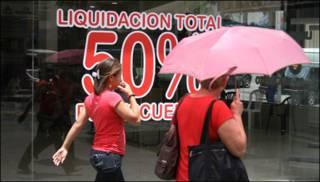 Compradoras frente a una vidriera de tienda en ofertas en Caracas, Venezuela.