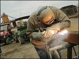 Soldador trabalha na construção do funil (ao fundo)