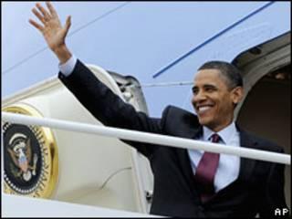 Президент США Барак Обама машет рукой, поднимаясь по трапу самолета