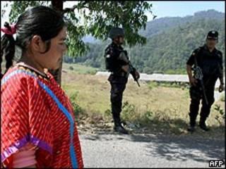 Indígena de la etnia triqui en México junto a soldado.