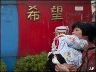 أم تحمل ابنها في حضانة في الصين