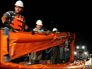 Trabajadores mueven mallas para contener el derrame de petróleo