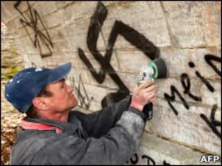 Муниципальный работник стирает свастику со стены в Павловске, Ленинградская область