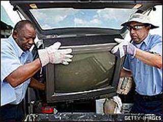 Dos hombres transportan un viejo televisor.