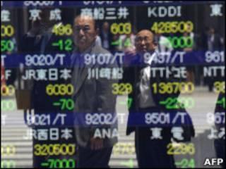 Homens observam quadro de cotações da Bolsa de Valores de Tóquio