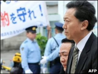 """Юкио Хатояма на фоне плаката """"Выполните обещание!"""""""
