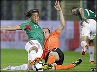 Jugador mexicano forcejeando con dos holandeses