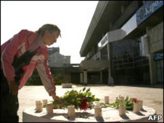 Женщина кладет цветы на месте взрыва