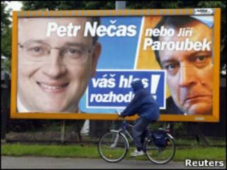 Велосипедист проезжает мимо предвыборного плаката