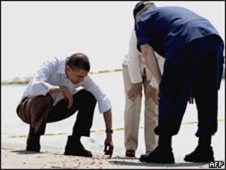 Барак Обама трогает песок на берегу Мексиканского залива