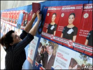 Женщина поправляет предвыборные плакаты в Тбилиси