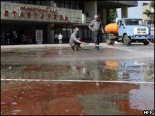 Рабочий смывает кровь с асфальта у концертного зала в Ставрополе