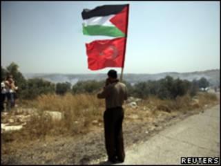 Activista palestino sostiene las banderas palestina y turca