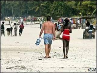 Khách du lịch đi trên bãi biển