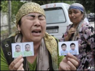 Плачущая женщина показывает фотографии детей