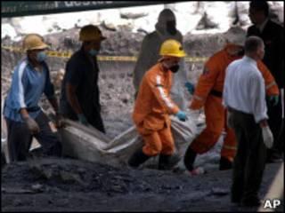 Los equipos de rescate sacan el cuerpo de uno de los fallecidos.