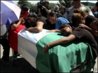 Mujeres lloran ante un ataúd con la bandera mexicana