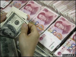 Foto de arquivo mostra funcionário de banco chinês manipulando dólares e yuans (Reuters)