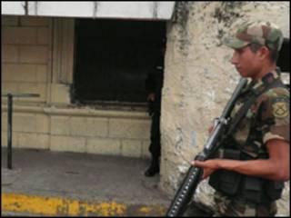 Un soldado patrulla las afueras del penal de Cojutepeque, en el departamento de Cuscatlán.