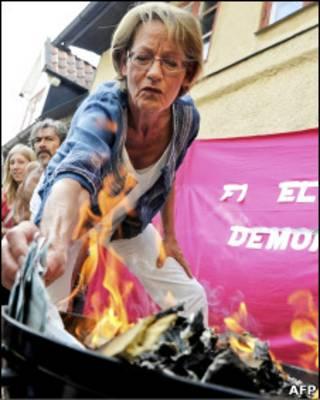 غودرون شيمان زعيمة حزب المبادرة النسوية في السويد تحرق المال احتجاجا على عدم تكافؤ الرواتب بين الرجال والنساء
