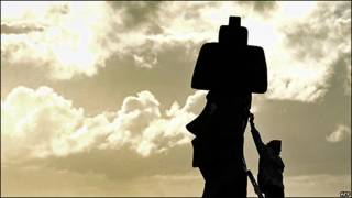 Un trabajador repara una estatua de la Isla de Pascua en la víspera del eclipse solar