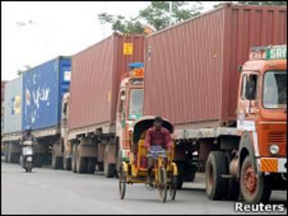 Homem passa com riquixá por caminhões em direção ao porto de Chennai, na Índia