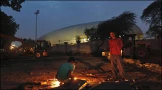 दिल्ली में जवाहरलाल नेहरू स्टेडियम के बाहर काम करते मज़दूर