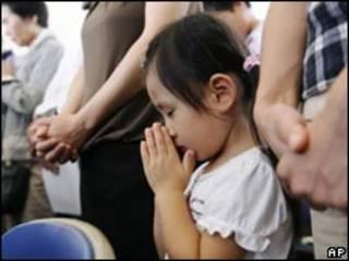 تصویری کودکی ژاپنی که در میان بزرگسالان به نیایش مشغول است