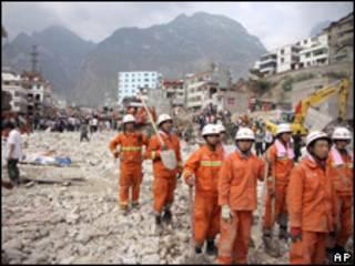 Homens trabalham em resgate de vítimas de deslizamentos na China (AP, 9 de agosto)