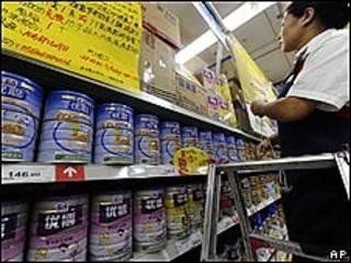 Una vendedora coloca latas de leche en polvo en un supermercado de Hefei, China.