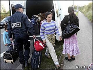 Un policía ayuda a una familia de gitanos a cargar sus pertenencias en un suburbio de Lille (Francia)