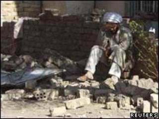 Homem senta-se em local atacado em Bagdá nesta quarta-feira (Reuters, 25 de agosto)