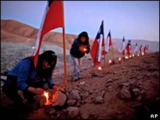 Mulheres acendem velas ao lado de 33 bandeiras para homenagear os mineiros presos