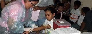 Practicando un examen de sangre en Siti del Niño.